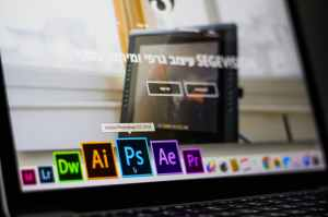 turned on laptop on desktop with hovered adobe photoshop cc application